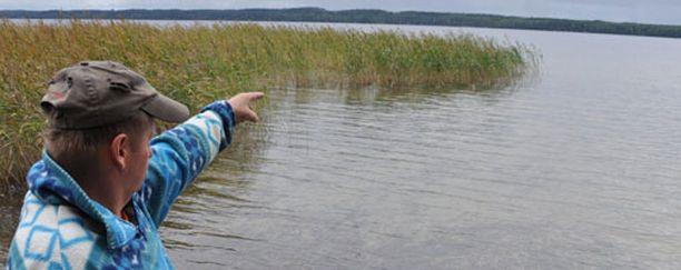 Poliisimiehen lapsuudenkaveri, maanviljelijä Jarmo Nykänen näyttää rannassa surmapaikkaa.