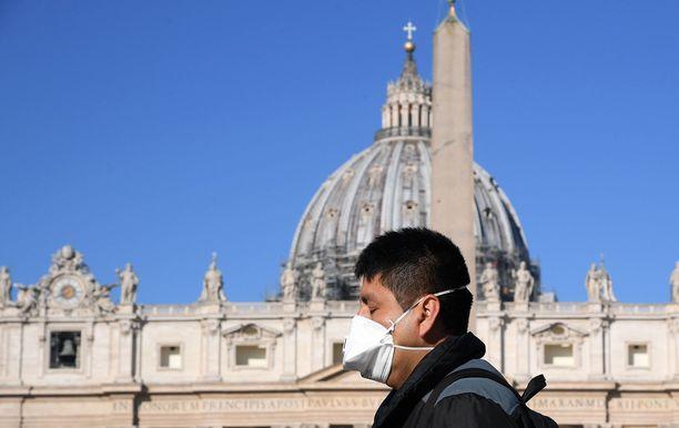 Koronakriisi on autioittanut Italian kadut. Mies suojautuu kasvomaskilla Roomassa 11.03.2020.