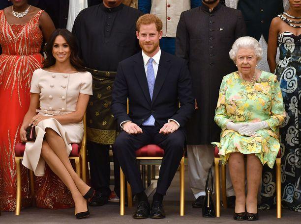 Meghan istuu visusti kuninkaallisen muodollisesti eikä ota malllia aviomiehestään, joka ottaa tilanteen paljon rennommin. Kuningatar näyttää hieman eristäytyneeltä. Meghanin tiukasti yhteen ristimät jalat ja laukun pitäminen sivulla viestivät, että hän ei tunne oloaan varmaksi, vaan pikemminkin kiusalliseksi.