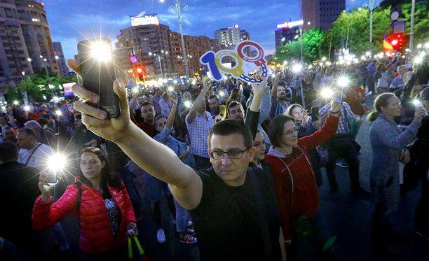 Mielenosoittajat nostavat puhelimensa ilmaan näyttäen taskulamppujen valoa Bukarestin mielenosoituksessa.
