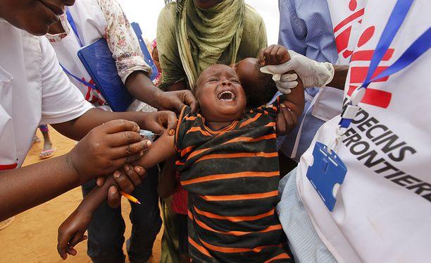 Lääkärit ilman rajoja-järjestön työntekijät rokottavat pikkupoikaa Somaliassa.