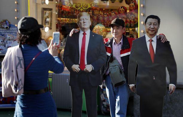Kiinalaisturistit ottamassa kuvia Donald Trumpin ja Kiinan presidentti Xi Jipingin pahvisista potreteista Moskovassa.