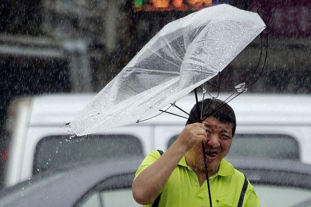 Mies taistelee taifuuni Lekimaa vastaan Taiwanin Taipeissa perjantaina 9. elokuuta 2019.