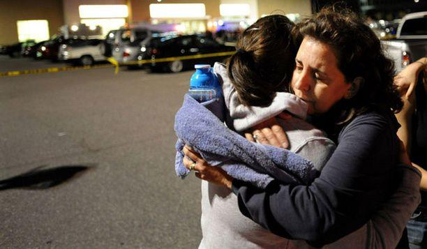 Äiti halaa ja lohduttaa tytärtään kuntokeskuksen edustalla.