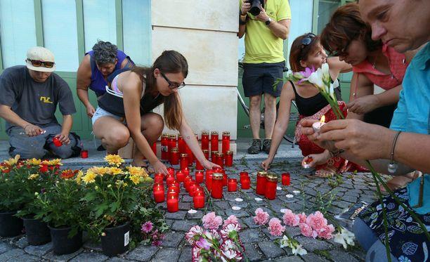 Ihmiset sytyttivät kynttilöitä kuolleiden pakolaisten muistoksi poliisiaseman edessä Itävallan Eisenstadtissa.