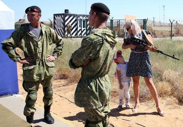 Venäläiset merimiehet katselevat, kun venäläisäiti kokeilee kivääriä lapsi vieresssään Astrahanissa Venäjällä.