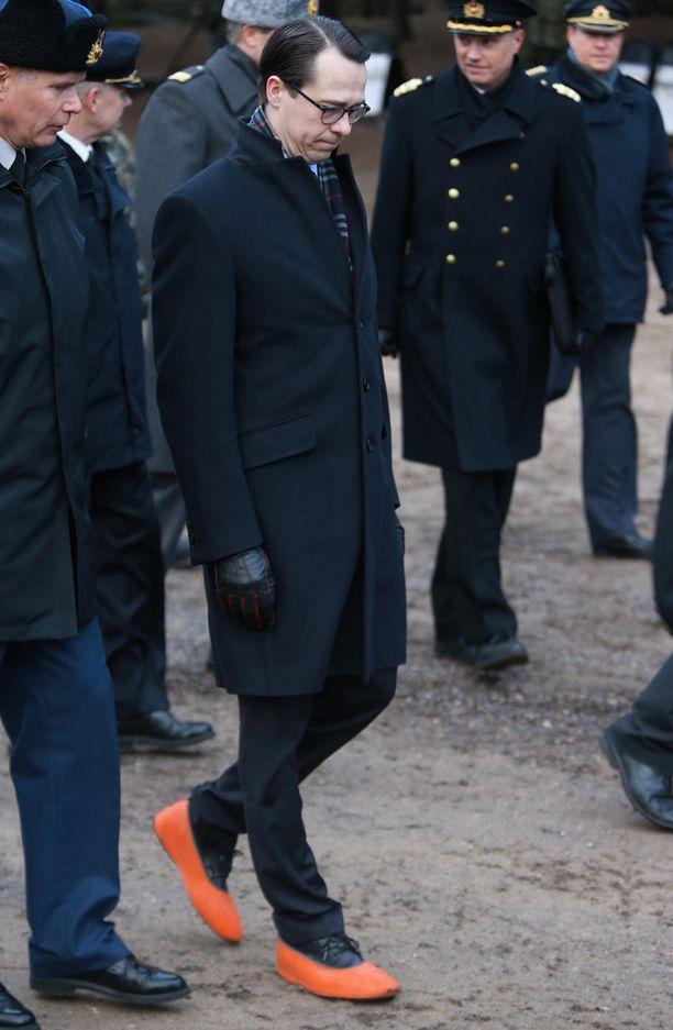 Puolustusministeri Carl Haglundin kenkiä suojasivat iloisen väriset kalossit.