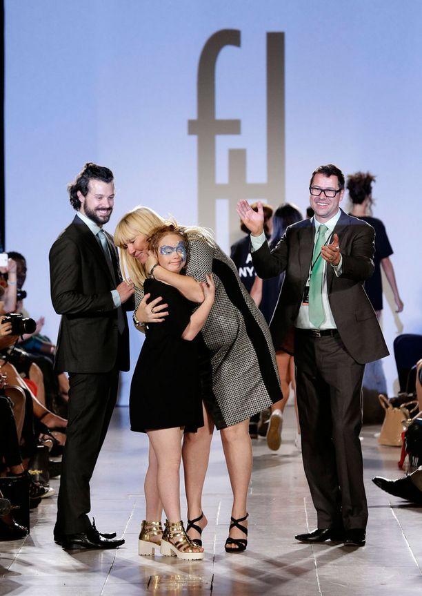 Rosanne Stuart halaa tytärtään näytöksen lopussa. Vasemmalla suunnittelija Hendrik Vermeulen sekä kumppani Jean-Daniel Meyer-Vermeulen.