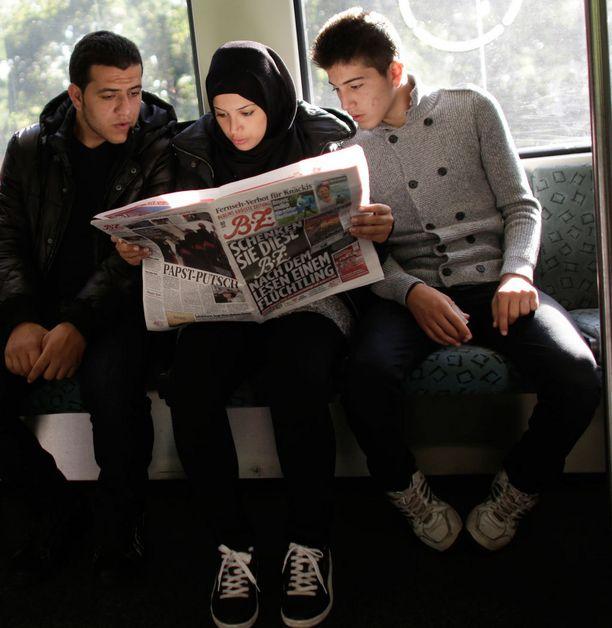 Syyrialaisperhe luki uutisia arabiankielisenäkin ilmestyneestä Berliner Zeitungistä Berliinissä.