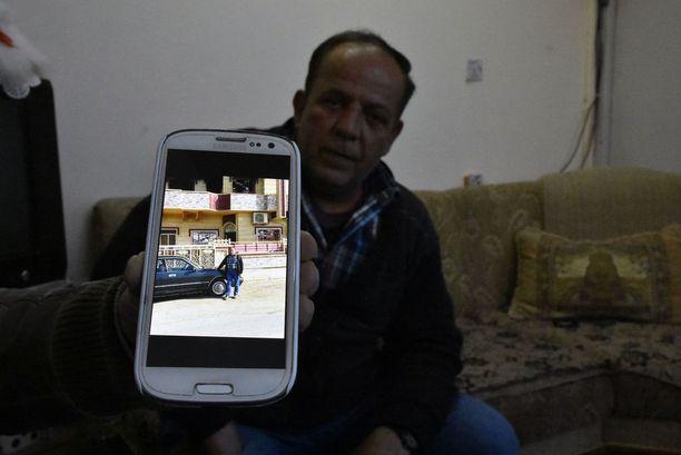 Mies kristittyjen pakolaisleirillä Erbilissä näyttää puhelimestaan, kuinka Isisin on tuhonnut hänen kotitalonsa Mosulin lähettyvillä.