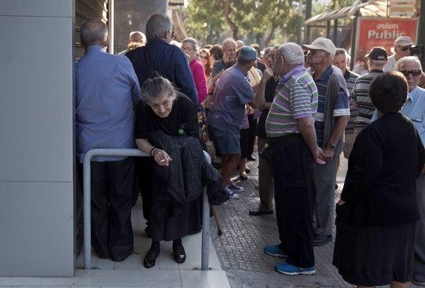 Kreikkalaiset eläkeläiset saavat eläkkeensä yleensä kuun lopussa. Joukko huolestunutta vanhempaa väkeä jonottikin maanantaina suljettujen pankkien ulkopuolella, sillä viranomaisten mukaan poikkeustilanne ei vaikuta eläkkeenmaksuun.
