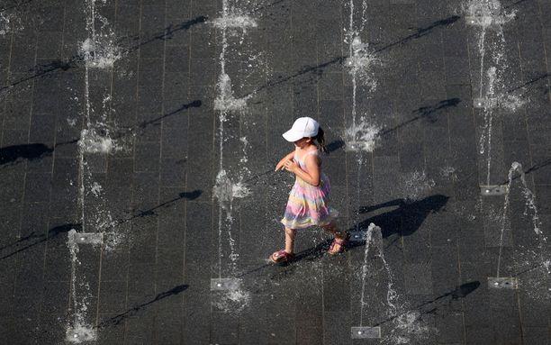 Lapsi leikki suihkulähteellä Saksan Duisburgissa kesäkuussa, jolloin maassa rikottiin uusi lämpöennätys, 38,6 astetta.
