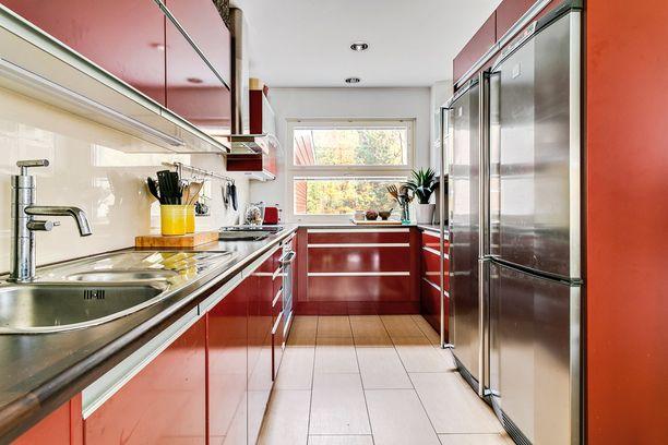 Punaisessa keittiössä ja teräspinnoissa on dynaamisuutta, joka herättää aamulla kodin unisimmankin henkilön. Käytännölliset suuret kaapit sopivat isomman perheenkin tarpeisiin.