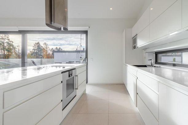 Valkoinen avara keittiö edustaa skandinaavista tyyliä.