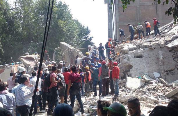 Sadat ihmiset saapuivat paikalle auttamaan eloonjääneitä romahtaneen kerrostalon raunioista.