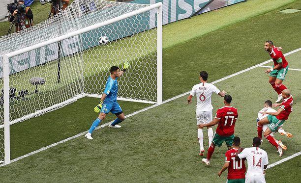 Cristiano Ronaldo (kaatumassa maahan) puskee voimalla Portugalin johtomaalin Marokon verkkoon.