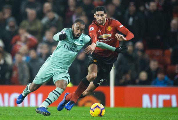 Marouane Fellaini tuli keskiviikon Arsenal-ottelussa kentälle 72. minuutilla. Kuvassa hän yrittää estää Alexandre Lacazetten etenemisen.