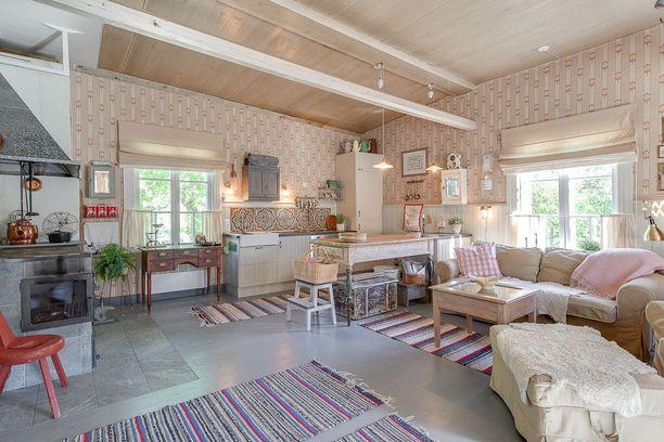 Tähän maalaistyyliseen keittiöön on valittu rohkeasti erilaisia materiaaleja ja kuvioita. Vanhat huonekalut sopivat tupaan loistavasti.