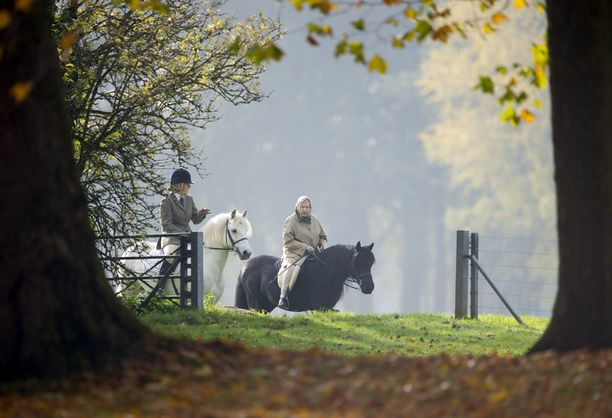 Yhdeksänkymppinen kuningatar ratsastelee leppoisasti huivi päässään.