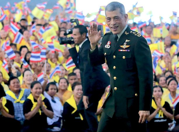 Kruunaamaton vt. kuningas Maha Vajiralongkorn vilkuttaa yleisölle viime joulukuussa uuden tekojärven avajaisissa. Hänen ei ole sallittu vielä kruunata itseään kuninkaaksi.
