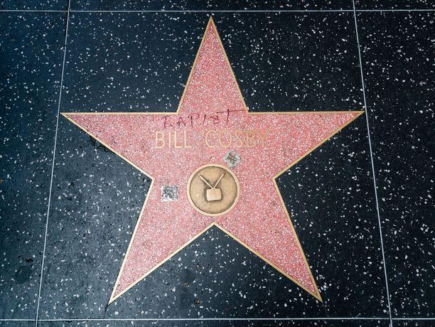 """Cosbyn tähti, jota on tuhrittu tussilla. Koomikon nimen yläpuolelle on kirjoitettu punaisella """"raiskaaja""""."""