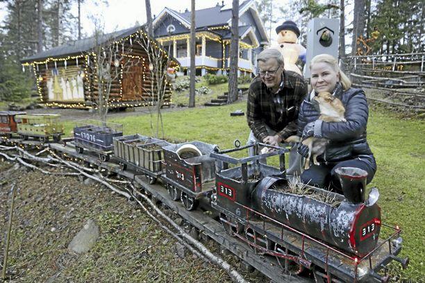 Kari Metso ja Niina Alander suunnittelevat jo, minkälaiset kukkaistutukset koristavat Karin tekemiä junia sekä muita pihan rakenteita ensi kesänä. Niinan sylissä on Dani-koira.