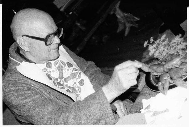 Kekkonen näyttää esimerkkiä, miten rapuja syödään. Presidentillä on päällään saunomisen jäljiltä yöpuku ja aamutakki.