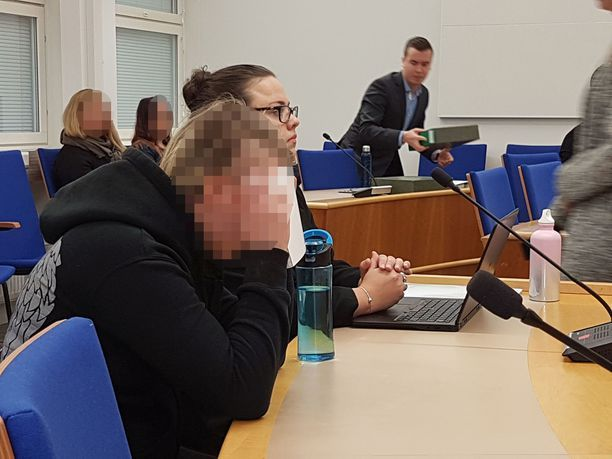 Toinen syytetyistä, nuori nainen, peitti kasvonsa oikeudessa. Kuva lokakuulta.