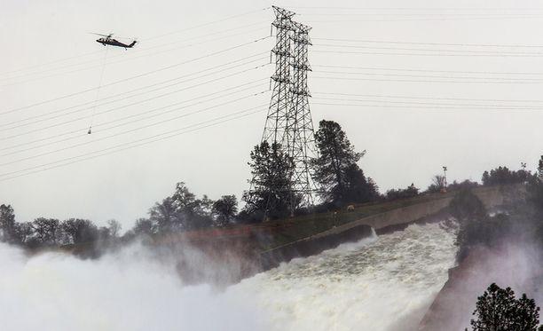 Helikopterit pudottavat kivillä täytettyjä säkkejä murtuneisiin kohtiin.