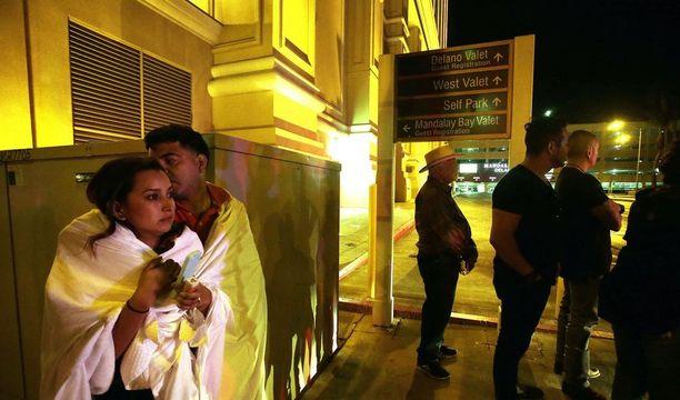 Pelastuneet ihmiset seisoivat Mandalay Bay -hotellin ulkopuolella lähellä rikospaikkaa Las Vegasissa.