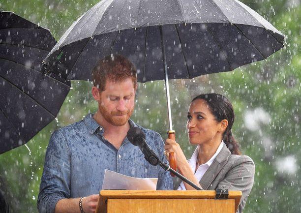 Prinssi Harry saa vaimoltaan apua sateen iskettyä Dubbon kaupunkiin. Meghan pitelee suloisesti sateenvarjoa miehelleen.