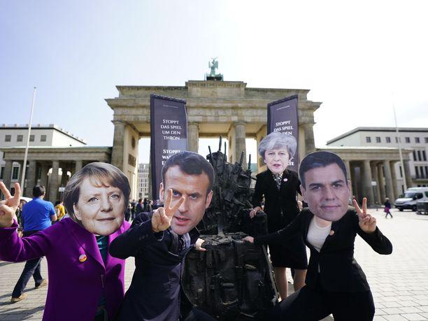 Game of Thrones vilisee myös politiikassa ja aktivismissa. Kuvassa asekauppaa vastustavat mielenosoittajat poseeraavat Berliinin Brandenmburgin portin edustalla Rautavaltaistuimen kanssa  viime viikonloppuna. Pahvikasvot esittävät Saksa Angela Merkeliä (vas.), Ranskan Emmanuel Macronia, Britannian Theresa Mayta ja Espanjan Pedro Sanchezia.