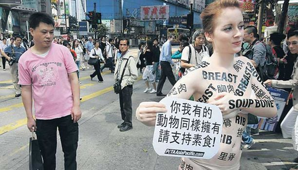 KETTUTYTTÖ Englantilainen eläinaktivisti varoitteli Hongkongissa kiinalaisia syömästä lihaa maalaamalla ruumiiseensa erilaisten herkkupalojen nimiä. Vasemmalla seisova kassimies on katseesta päätellen varmasti lihansyöjä, joka arvostaa erityisesti kinkkua.