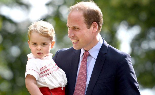 Prinssi George isänsä prinssi Williamin sylissä pikkusiskonsa prinsessa Charlotten ristiäisissä viime heinäkuussa. Pikku prinssi on arvatenkin syynä George-nimen suosion nousuun Britanniassa. Käyköhän samoin myös Charlotten kohdalla?