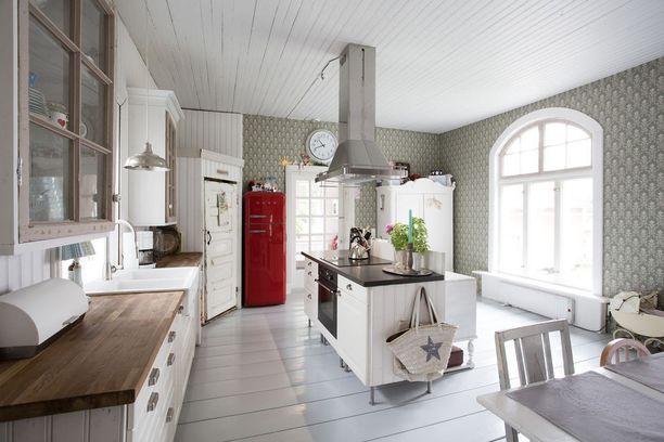 Suuren keittiön keskellä oleva saareke kutsuu isommankin joukkion kokkauspuuhiin. Kaari-ikkunasta valo tulvii sisään ja pienikuvioinen tapetti tuo maalaisromanttista tunnelmaa.
