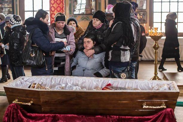 Zhanna Molodetskykh poikansa Igorin hautajaisissa avoimen arkun äärellä.