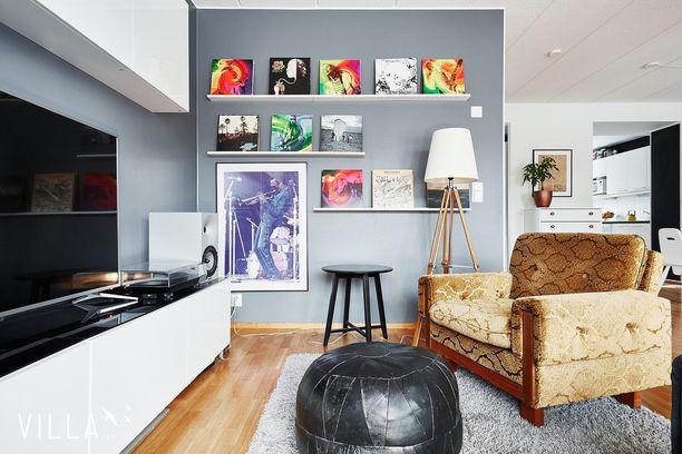 Näin yksinkertaisella tavalla voi tuoda väriä kotiinsa: hyllyille asetettujen vinyylilevyjen avulla. Kotiin tuo eloa myös siniseen taittava harmaa seinä.