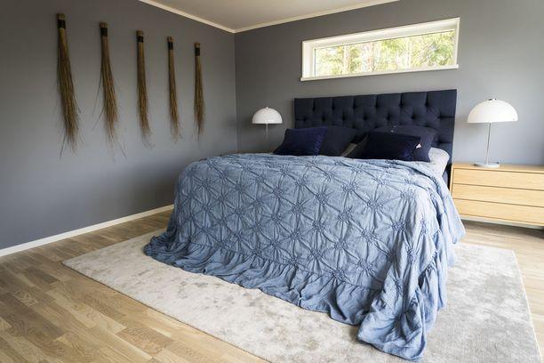 Yönsinisen sängynpäädyn värit toistuvat tyynyjen väreissä. Asuntomessukohde 15.