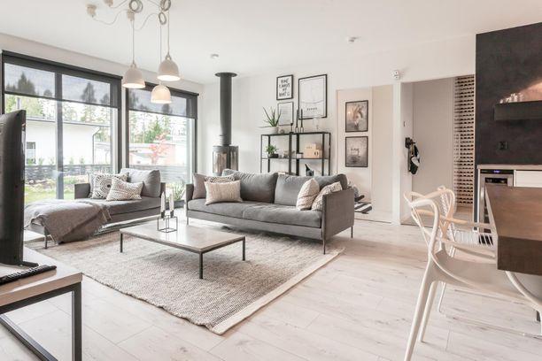 Sisätiloissa ei puu perinteisine sävyineen näy. Olohuoneen ja avokeittiön yhdistelmässä katse kiinnittyy harmonisen sisustuksen lisäksi betonitasoihin, kalkkimaalattuihin seiniin ja laminaattilattiaan.