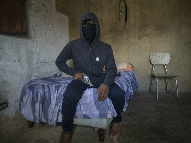 Venezuelan valtiolla ei ole varaa aseisiin sen enempää kuin gangstereillakaan. Kuvassa katujengiläinen El Negrito, 24.