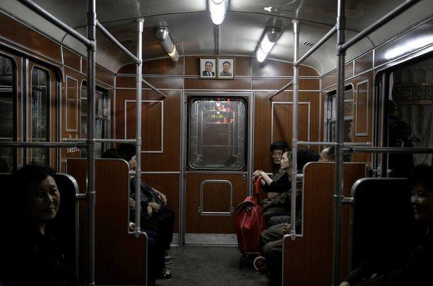 Länsitoimittajat pääsivät metroon, jonka vaunua koristivat Kim Il-sungin ja Kim Jong-ilin potretit.