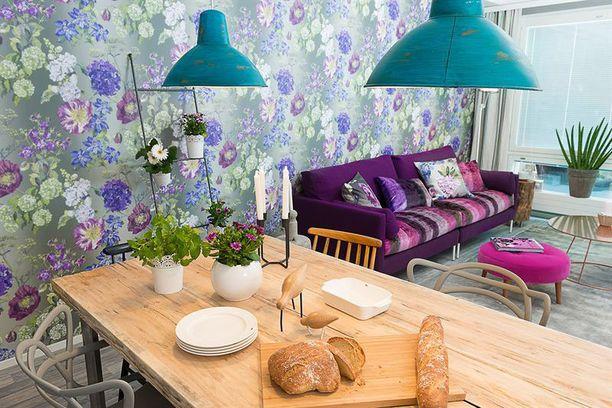 Ellenin suunnittelemassa olohuoneessa on näyttävä kukkatapetti. Sisustuksen kiintopiste on myös vanhasta punahongasta teetetty kookas ruokapöytä.