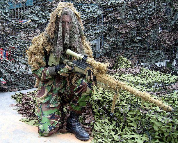 Tarkka-ampuja poseeraa L115A-kiväärin kanssa.