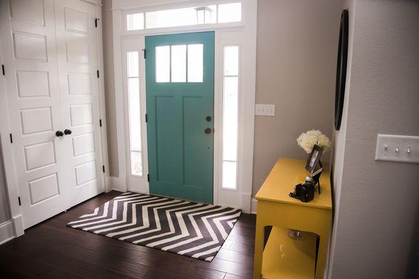 Tämä harmaasävyinen eteinen piristyy kummasti, kun ovi on vihreänsininen.