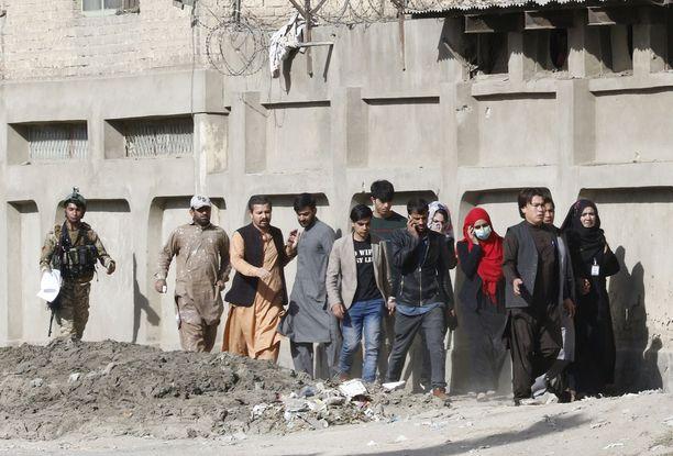 Siviileille Afganistan on vaarallinen. Kuvassa Afganistanin erikoisjoukkojen sotilas saattaa TV-toimittajia turvaan sen jälkeen, kun militiaryhmä hyökkäsi TV-asemalle Kabulissa 7. marraskuuta.