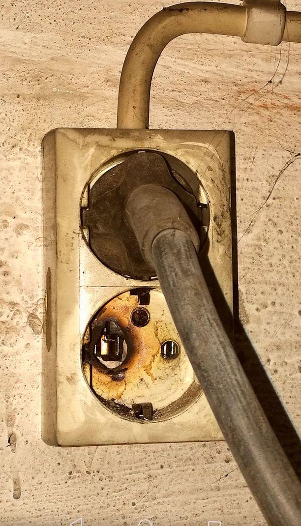 Kuvassa löystynyt liitos pistorasiassa. Löystyneen liitoksen takia muovi on sulanut.