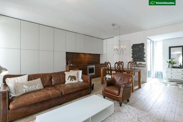 Tässä kodissa avokeittiö ja olohuone sulautuvat tyylikkäästi yhteen. Eleettömät kaapistot sopivat molempien huoneiden tunnelmaan ja tuovat reilusti lisätilaa huoneeseen.