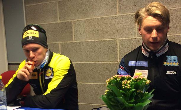 Perttu Hyvärisen lehdistösaliin kiikuttama kisamakkara maistui Matti Heikkiselle. Oikealla mestaruuteen hiihtänyt Anssi Pentsinen.