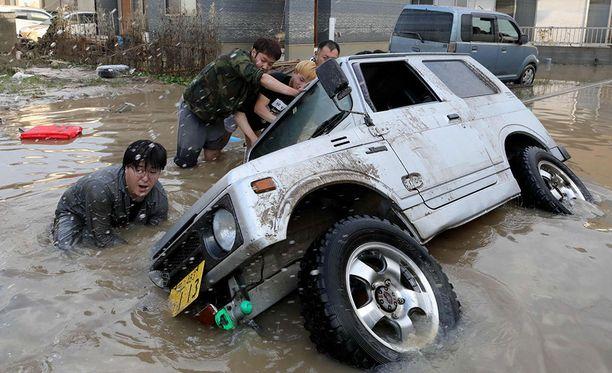 Japanin Okayamassa asukkaat yrittävät nostaa upoksissa olevaa autoa. Rankkasateet ovat koetelleet erityisen rankasti Japanin keski- ja länsiosia.