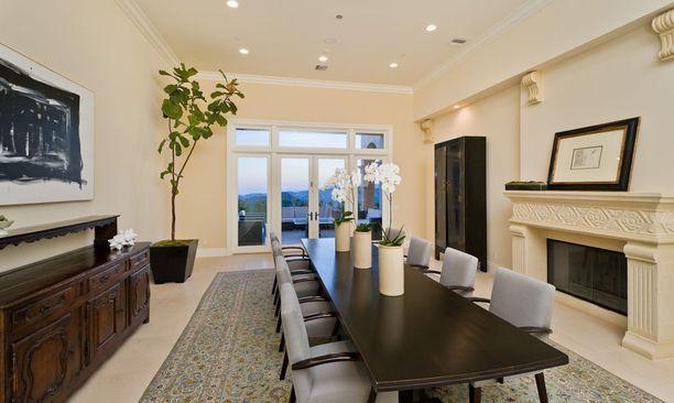 Ruokailuhuoneen sisustuksessa on yhdistetty uutta ja vanhaa. Pariovet vievät terassille komeisiin maisemiin.